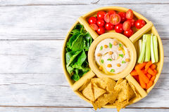 Healthy homemade delicious spicy hummus with baby carrots, celery sticks, spinach, ginger, sliced lime, virgin olive oil, pine nut Royalty Free Stock Photo