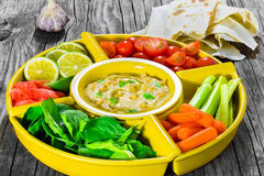 Healthy homemade delicious spicy hummus with baby carrots, celery sticks, spinach, ginger, sliced lime, virgin olive oil, pine nut Royalty Free Stock Image