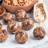 Healthy homemade energy balls with cranberries, nuts, dates and rolled oats on a parchment, square format Royalty Free Stock Photos