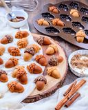 Healthy homemade Maple Acorn Cakelets on wood slice serving board, tray. Healthy homemade Maple Acorn Cakelets, acorn shape cookies on wood slice serving board Royalty Free Stock Image