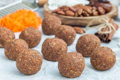 Healthy homemade paleo energy balls with carrot, nuts, dates and coconut flakes, on a parchment, horizontal Royalty Free Stock Image