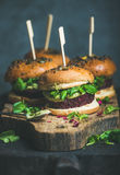 Healthy homemade vegan burger with beetroot-quinoa patty, arugula, avocado sauce stock images