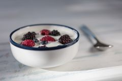 Healthy homemade yoghurt with fresh blueberries, raspberries a. Nd blackberries with early summer morning light, shallow depth of field stock photography