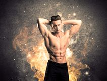 Healthy hot male showing muscles with fire. A strong athletic guy looking seductive while working out with weight in front of a burning fire concrete wall and Stock Photos