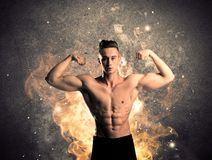 Healthy hot male showing muscles with fire. A strong athletic guy looking seductive while working out with weight in front of a burning fire concrete wall and Royalty Free Stock Images