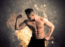 Healthy hot male showing muscles with fire. A strong athletic guy looking seductive while working out with weight in front of a burning fire concrete wall and Stock Image