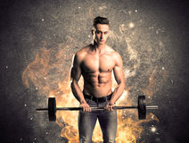 Healthy hot male showing muscles with fire. A strong athletic guy looking seductive while working out with weight in front of a burning fire concrete wall and Stock Photo