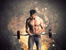 Healthy hot male showing muscles with fire. A strong athletic guy looking seductive while working out with weight in front of a burning fire concrete wall and Stock Images