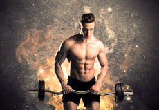 Healthy hot male showing muscles with fire. A strong athletic guy looking seductive while working out with weight in front of a burning fire concrete wall and Royalty Free Stock Photography