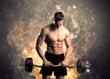 Healthy hot male showing muscles with fire. A strong athletic guy looking seductive while working out with weight in front of a burning fire concrete wall and Royalty Free Stock Photo