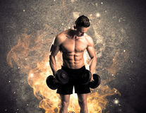 Healthy hot male showing muscles with fire. A strong athletic guy looking seductive while working out with weight in front of a burning fire concrete wall and Royalty Free Stock Photos
