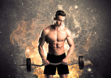 Healthy hot male showing muscles with fire. A strong athletic guy looking seductive while working out with weight in front of a burning fire concrete wall and Stock Photography