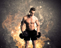 Healthy hot male showing muscles with fire. A strong athletic guy looking seductive while working out with weight in front of a burning fire concrete wall and Royalty Free Stock Image