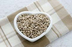Nutritional Hulled Sunflower Seeds. Healthy hulled organic sunflower seeds in a heart shaped bowl on napkin.  Overhead view and close up Royalty Free Stock Images