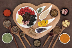 Healthy Immune Boosting Food. Superfood immune boosting selection in white porcelain dishes and wooden bowls over heart shaped board and lokta paper background stock photo