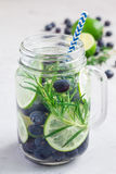 Healthy infused water with fresh blueberry, lime and rosemary, vertical Royalty Free Stock Images