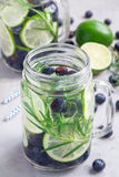 Healthy infused water with fresh blueberry, lime and rosemary, vertical Stock Photography