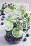 Healthy infused water with fresh blueberry, lime and rosemary, vertical Stock Photos