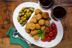 Healthy italian appetizer with risotto balls arancini , green ol. Ives , Tomato and red Wine Royalty Free Stock Photography