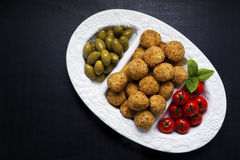 Healthy italian appetizer with risotto balls arancini , green ol. Ives , Tomato and red Wine Royalty Free Stock Photos