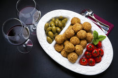 healthy italian appetizer with risotto balls arancini , green olives , tomato and red wine royalty free stock image