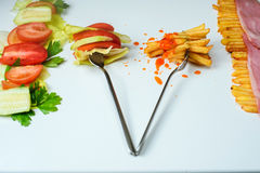 Healthy or junk food choice. Two forks: one with french fries and another with fresh vegetables stock photo