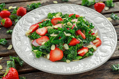 Healthy kale salad with strawberries and almond in a plate on wooden table Royalty Free Stock Photography