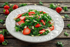Healthy kale salad with strawberries and almond in a plate on wooden table Royalty Free Stock Image