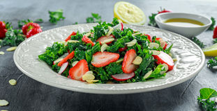 Healthy kale salad with strawberries and almond in a white plate Stock Photo