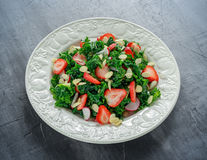 Healthy kale salad with strawberries and almond in a white plate stock images