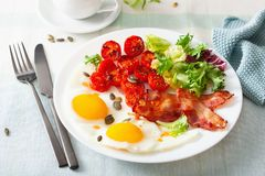 Healthy keto diet breakfast: egg, tomatoes, salad leaves and bacon stock images