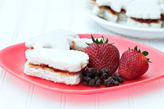 Healthy kid's meal. A healthy kid's meal of peanut butter and jelly sandwiches, strawberries and raisins. Sandwiches are in fun summer shapes of feet, pineapple Stock Photo