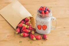 Healthy layered dessert with chia pudding, strawberry and honeys. Uckle in a mason jar on rustic background Royalty Free Stock Image