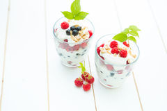 Healthy layered dessert with cream, muesli, raspberries and currants. On wooden background with space for text Stock Images