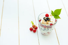 Healthy layered dessert with cream, muesli, raspberries and currants. On wooden background with space for text Stock Photo