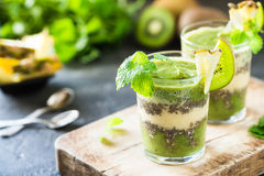 Healthy layered smoothie with kiwi, pineapple, chia. Seeds, mint. Two glasses on wooden board, dark background Stock Photography