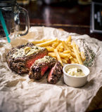 Healthy lean grilled medium-rare steak with french fries, beer. Healthy lean grilled medium-rare steak with french fries, and beer, and a spice in a rustic pub stock photography