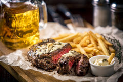 Healthy lean grilled medium-rare steak with french fries, beer. Healthy lean grilled medium-rare steak with french fries, and beer, and a spice in a rustic pub royalty free stock photo