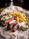 Healthy lean grilled medium-rare steak with french fries, beer. Healthy lean grilled medium-rare steak with french fries, and beer, and a spice in a rustic pub stock photo