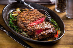 Healthy lean grilled medium-rare steak and vegetables. With whiskey glass and a spice in a rustic pub or tavern. Food-styling royalty free stock photo