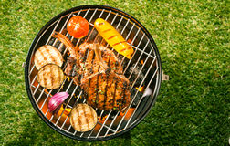 Healthy lean pork loin with veggies on a BBQ. Healthy lean pork loin cutlets with assorted fresh veggies grilling over the glowing coals on a BBQ outdoors on the Stock Photo