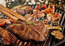 healthy lean t-bone steak grilling on a BBQ Stock Images