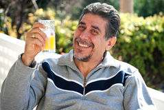 Healthy life. A man drinking a glass of fresh orange juice during a sunny day Royalty Free Stock Photography