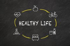 `Healthy life` text and icons on a blackboard. stock photo