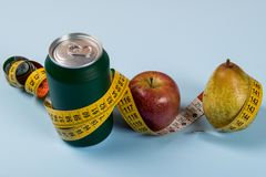 Healthy life contrast with can of soda and fruit with a tape measure.  royalty free stock image