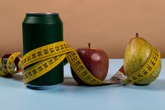 Healthy life contrast with can of soda and fruit with a tape measure.  royalty free stock photos