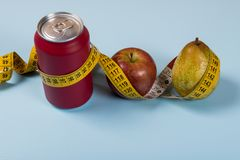 Healthy life contrast with can of soda and fruit with a tape measure.  stock photography