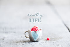 Healthy life idea - text, raspberry and cup with a heart. Ripe raspberry in a cup on the table and text healthy life Royalty Free Stock Photo