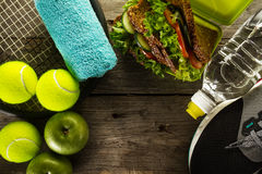 Healthy Life Sport Concept. Sneakers with Tennis Balls, Towel, A. Pples, Healthy Sandwich and Bottle of Water on Wooden Background. Copy Space. Above Stock Image
