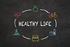 `Healthy life` text and colourful icons on a blackboard. royalty free illustration